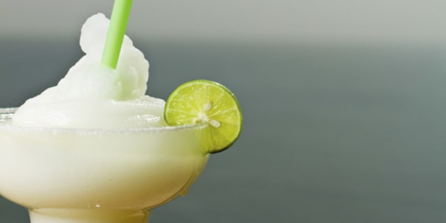 Frozen Margarita with lime and straw at a bar by the ocean