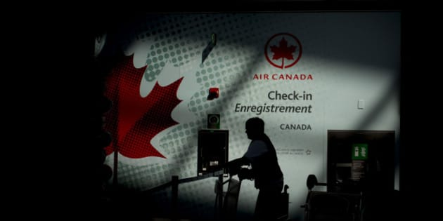 The silhouette of an Air Canada employee is seen pushing a buggy near a check-in counter at Toronto Pearson International Airport in Toronto, Ontario, Canada, on Wednesday, July 3, 2013. Air Canada predicted further pressure on fares this year after its first-quarter yield dropped as competitors added seating and offered lower prices on some routes in North and South America. Photographer: Brent Lewin/Bloomberg via Getty Images