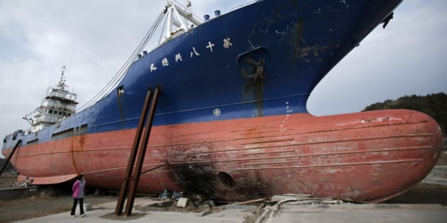A woman looks at a vessel swept inland by the tsunami following the Great East Japan Earthquake in Kesennuma, Miyagi Prefecture, Japan, on Sunday, March 10, 2013. Japan's economy grew at an annualized 0.2 percent last quarter after shrinking 3.7 percent the three previous months, the worst since the 2011 earthquake, revised government data show. Photographer: Kiyoshi Ota/Bloomberg via Getty Images