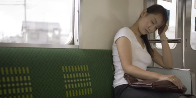Young woman sitting on train holding bag on lap, eyes closed