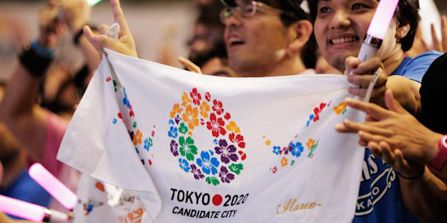 TOKYO, JAPAN - SEPTEMBER 08:  Residents of Olympic bid city Tokyo celebrate while holding Tokyo signs after the announcement of the 2020 Summer Olympic Games host city at Komazawa Olympic Park on September 8, 2013 in Tokyo, Japan. Madrid was the first city to be eliminated, followed by Istanbul. Tokyo won the right to host the 2020 Summer Olympic Games in the final ballot.  (Photo by Adam Pretty/Getty Images)