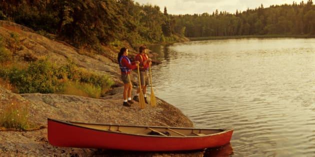couple with canoe along Big Whiteshell Lake, Whiteshell Provincial Park, Manitoba, Canada
