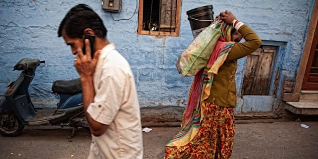 Man talking on mobile phone and woman carrying bags on her head in a typical blue street in old town. Jodhpur, Rajasthan, India