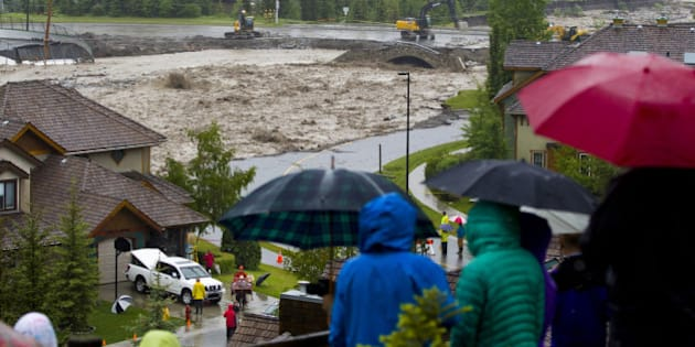 CANMORE, CANADA - JUNE 20:  Residents watch the flooding Cougar Creek as it takes out Eagle Terrace Road (C) and nears the top of the Elk Run Blvd Bridge June 20, 2013 in Canmore, Alberta, Canada. Widespread flooding caused by torrential rains washed out bridges and roads prompting the evacuation of thousnds.  (Photo by John Gibson/Getty Images)