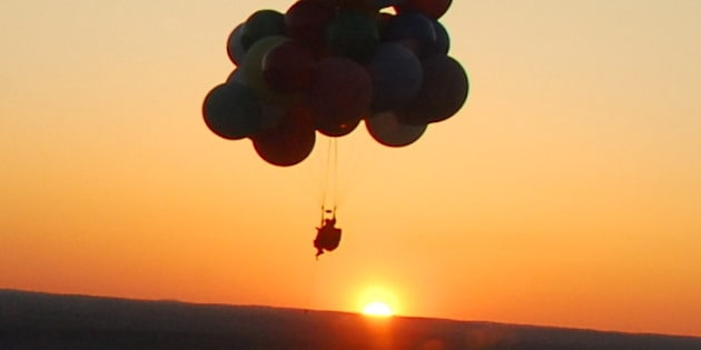 RALEIGH, NC - APRIL 10: EXCLUSIVE. Jonathan Trappe at sunset as he attempts of the world's first day/night cluster balloon flight in addition to attempting to break known endurance records on April 10, 2010 in Raleigh, North Carolina. Taking off at 5.35pm on Saturday 10th April from Raleigh Executive Jet Port in North Carolina, cluster balloonist Jonathan Trappe begins his attempt of the world's first day/night cluster balloon flight in addition to attempting to break known endurance records. Flying 8,000 feet up for nearly 14 hours, Jonathan landed at 7.10am on Sunday 11th April having completed both feats. Braving the freezing temperatures, Jonathan flew for 109 miles during his adventure. Constantly monitored from below by his team, led by his girlfriend, Jonathan has been cluster ballooning for only four years. (Photo by Jonathan Trappe/ Barcroft USA / Getty Images)