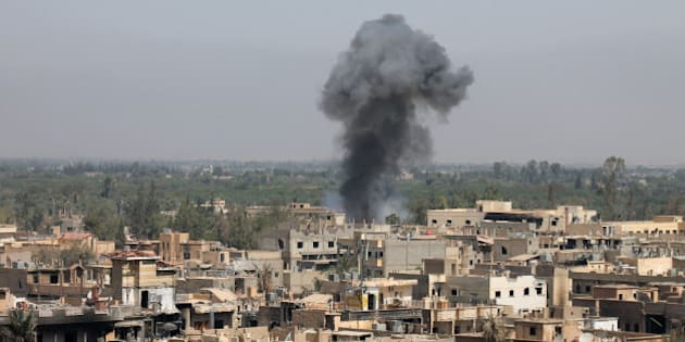 A photo taken on August 13, 2013 shows smoke billowing from buildings in Syria's eastern town of Deir Ezzor following an airstrike by government forces. Syrian opposition activists, including National Coalition members, have drawn up a transitional roadmap including a call for national reconciliation and justice for 'all of Syria's victims,' a statement said. AFP PHOTO / ABO SHUJA        (Photo credit should read ABO SHUJA/AFP/Getty Images)