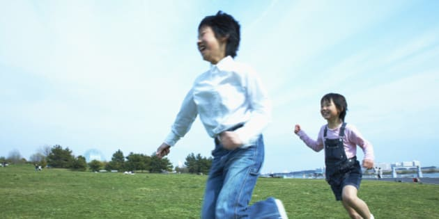 Boy and girl (8-9) running in park