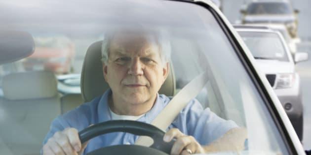 Elderly man driving car in traffic