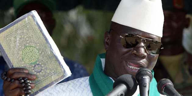 Serekunda, GAMBIA:  Gambia's President and leader of the Alliance for Patriotic Reorientation and Construction party, Yahya Jammeh, holds the Koran during a presidential campaign meeting 20 September 2006 in Serekunda. Gambians go to the polls 22 September 2006 in a presidential vote expected to give incumbent Yahya Jammeh a third term as head of this tiny West African state, in the face of a weak opposition. AFP PHOTO SEYLLOU   (Photo credit should read SEYLLOU/AFP/Getty Images)