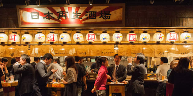 Customers dine at a pub in Tokyo, Japan, on Monday, Dec. 10, 2012. Japan's economy shrank in the last two quarters, meeting the textbook definition of a recession, as the dispute with China, the country's biggest export market, caused consumers there to shun Japanese products and contributed to Japan's worst year for exports since the global recession in 2009. Photographer: Noriko Hayashi/Bloomberg via Getty Images