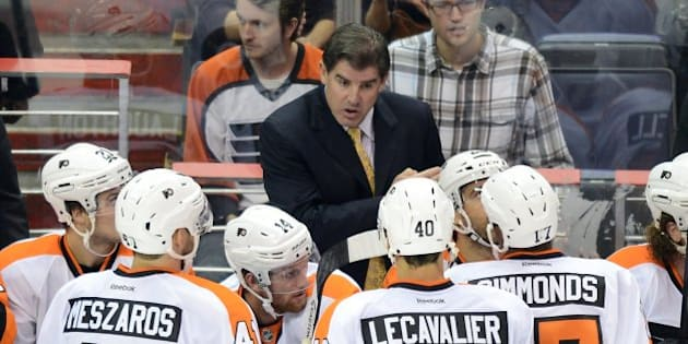 Philadelphia Flyers head coach Peter Laviolette speaks with his players in the third period of a preseason game against the Washington Capitals at the Verizon Center in Washington, D.C., Friday, September 27, 2013. The Capitals defeated the Flyers, 6-3. (Chuck Myers/MCT via Getty Images)