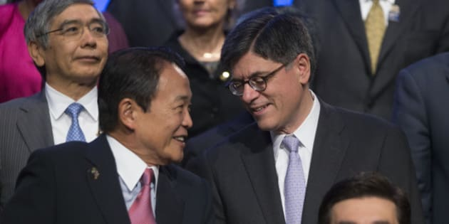 Jacob 'Jack' Lew, U.S. treasury secretary, right, talks to Taro Aso, Japan's finance minister, during the Group of 20 nations (G-20) finance ministers and central bank governors family photograph on the sidelines International Monetary Fund and World Bank Group Annual Meetings in Washington, D.C., U.S., on Friday, Oct. 11, 2013. Any measures by Asian policy makers to implement capital controls on outflows could backfire and officials should focus on easing existing restrictions on money entering their economies, the IMF said today. Photographer: Andrew Harrer/Bloomberg via Getty Images