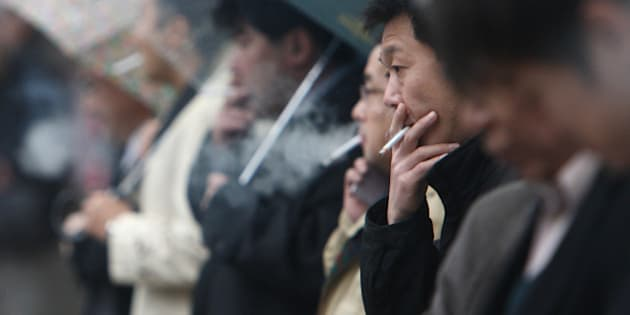 People smoke cigarettes in Tokyo, Japan, on Friday, Dec. 11, 2009. Yoshiyasu Okihira, an analyst at Credit Suisse, said on Dec. 4 he expects the Japanese government to raise tobacco taxes by 40-60 yen a pack after a media report by the Mainichi Daily News. Photographer: Tomohiro Ohsumi/Bloomberg via Getty Images