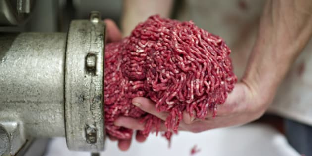 Butcher Justin Taylor collects ground beef as it exits the grinder at the Wyanet Locker in Wyanet, Illinois, U.S., on Thursday, April 26, 2012. Cattle futures rose for a second day on signs that the biggest buyers of U.S. beef will keep purchasing the meat, even after the country reported its first case of mad cow disease in six years. Photographer: Daniel Acker/Bloomberg via Getty Images