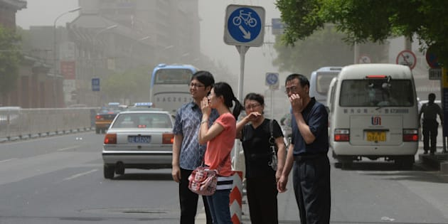People try to protect themselves against air pollution and dust along a street in Beijing on May 19, 2013.  China will more than double the number of cities covered by air quality monitoring, as part of efforts to tackle heavy smog that has sparked huge public anger. Swathes of acrid haze have repeatedly shrouded large parts of the country in recent months, provoking outrage among Internet users and unusual outspoken calls for action, in the state-run media.     AFP PHOTO / Mark RALSTON        (Photo credit should read MARK RALSTON/AFP/Getty Images)