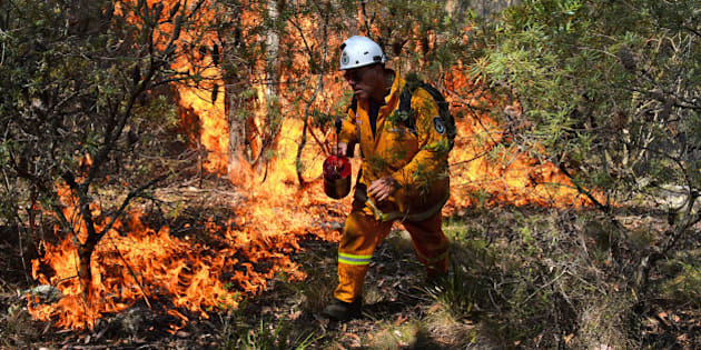 A firefighter lights a back burn near Mount Victoria in the Blue Mountains on October 21, 2013, as volunteer fire brigades race to tame an enormous blaze, with officials warning it could merge with others to create a 'mega-fire' if weather conditions worsen.  Crews have been battling fires that flared in high winds and searing heat across the state of New South Wales last week with more than 200 homes so far destroyed and many others damaged.  AFP PHOTO/William WEST        (Photo credit should read WILLIAM WEST/AFP/Getty Images)