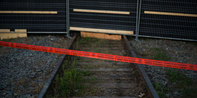 LAC-MEGANTIC, CANADA - JULY 14:  Police tape marks the outside boundary of the 'red zone' crash site, on July 14, 2013 in Lac-Megantic, Quebec, Canada. A train derailed and exploded into a massive fire that flattened dozens of buildings in the town's historic district, leaving 60 people dead or missing in the early morning hours of July 6.  (Photo by Ian Willms/Getty Images)