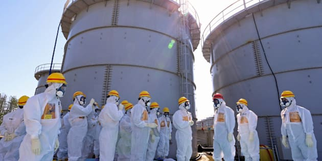 Shinzo Abe, Japan's prime minister, third right wearing a red helmet, is briefed by Akiro Ono, plant chief for the Tokyo Electric Power Co. (Tepco) Fukushima Dai-ichi nuclear power plant, as they stand in front of storage tanks for radioactive water at the Tepco Fukushima Dai-ichi nuclear power plant in Okuma, Fukushima Prefecture, Japan, on Thursday, Sept. 19, 2013. Abe on a visit to the wrecked Fukushima Dai-Ichi atomic station told Tokyo Electric Power Co. its priority is to halt leaks of radioactive water from the plant into the ocean. Source: Japan Pool via Bloomberg