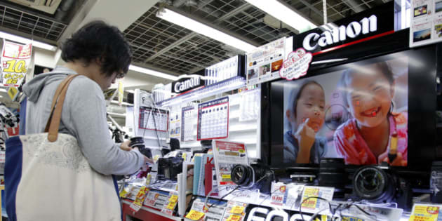 A customer looks at Canon Inc. digital cameras at an electronics store in Tokyo, Japan, on Thursday, Oct. 25, 2012. Canon, the world?s largest camera maker, cut its full-year profit forecast after a sluggish global economy damped sales, China production was disrupted and a stronger yen eroded the value of exports. Photographer: Kiyoshi Ota/Bloomberg via Getty Images
