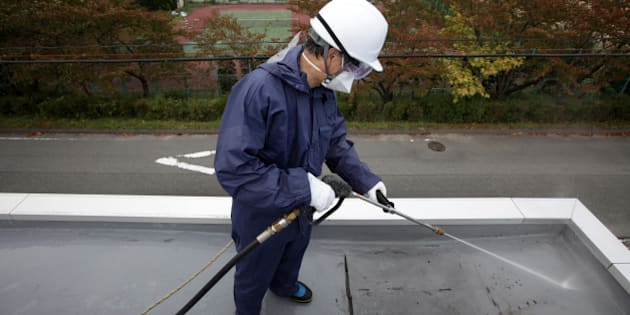 A worker sprays high pressure water during a decontamination process at a kindergarten in Hirono Town, Fukushima Prefecture, Japan, on Monday, Oct. 17, 2011. Japan's environment ministry will budget more than 1.1 trillion yen for decontamination by the end of the next fiscal year, Goshi Hosono, minister in charge of the response to the nuclear crisis, said Sept. 30. Photographer: Tomohiro Ohsumi/Bloomberg via Getty Images