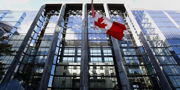 The Canadian flag flies outside the Bank of Canada building in Ottawa, Ontario, Canada, on Wednesday, Oct. 23, 2013. Bank of Canada Governor Stephen Poloz surprised investors by dropping language about the need for future interest rate increases that had been in place for more than a year, citing greater slack in the economy, while keeping his main policy rate unchanged. Photographer: Patrick Doyle/Bloomberg via Getty Images