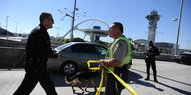 A K-9 officer (L) crosses a crime tape line on November 1, 2013 after a gunman reportedly opened fire at a security checkpointin Los Angeles International Airport. Police believe a gunman who opened fire at Los Angeles airport Friday acted alone, a police chief said, while not confirming reports that the shooter and one victim were killed. 'We believe at this point that there was a lone shooter, that he acted,' said Patrick Gannon, head of the LAX police force, saying he 'was the only person who was armed in this incident.' Seven people were injured, including six taken to hospital, said the head of the LA Fire Department James Featherstone, briefing reporters for the first time a couple of hours after the incident. AFP PHOTO/ROBYN BECK        (Photo credit should read ROBYN BECK/AFP/Getty Images)