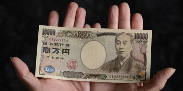 A Japanese 10,000 yen banknote is arranged for a photograph in Kawasaki, Kanagawa Prefecture, Japan, on Tuesday, July 9, 2013. Economists are ditching forecasts for the Bank of Japan to further expand its record easing this year amid signs that a recovering economy may spur inflation. Photographer: Akio Kon/Bloomberg via Getty Images