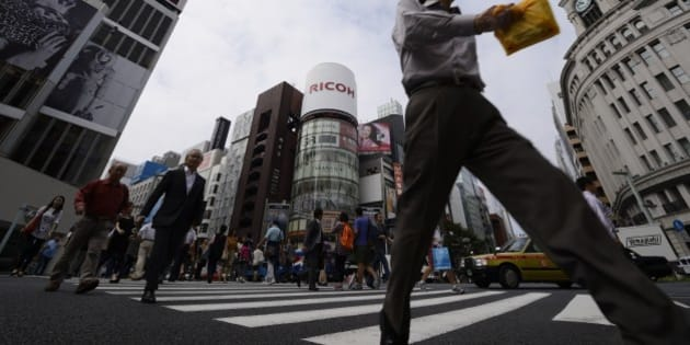 Pedestrians cross a street in the Ginza district of Tokyo, Japan, on Monday, Sept. 30, 2013. Large Japanese manufacturers confidence jumped more than economists forecast, bolstering the case for Prime Minister Shinzo Abe to press ahead with an increase in the nations sales tax. Photographer: Akio Kon/Bloomberg via Getty Images