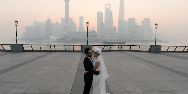SHANGHAI, CHINA - NOVEMBER 07:  (CHINA OUT) A newlywed couple takes wedding photos at the Bund as heavy smog engulfs the city on November 7, 2013 in Shanghai, China. People were advised to stay indoors today as the Shanghai Environment Agency measured air pollution levels at five out of a possible six.  (Photo by ChinaFotoPress/ChinaFotoPress via Getty Images)