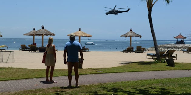 In this photograph taken on September 29, 2013, tourists watch Indonesian military helicopters patroling the beach area of Nusa Dua, close to the venue of the Asia-Pacific Economic Cooperation (APEC) summit in Indonesia's resort island of Bali. Indonesian authorities have increased security ahead of the APEC summit where 21 world leaders including US President Barack Obama will participate in the leaders summit from October 7 to 8.  AFP PHOTO / ROMEO GACAD        (Photo credit should read ROMEO GACAD/AFP/Getty Images)