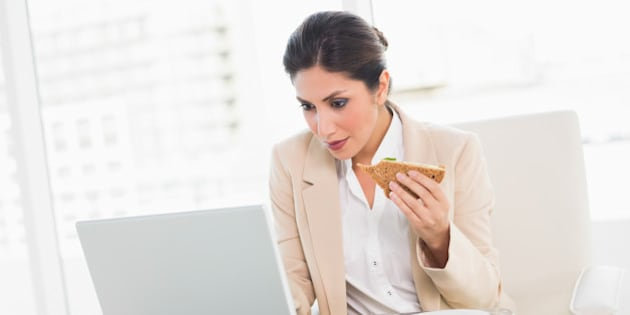 Focused businesswoman eating lunch as she is working at the office