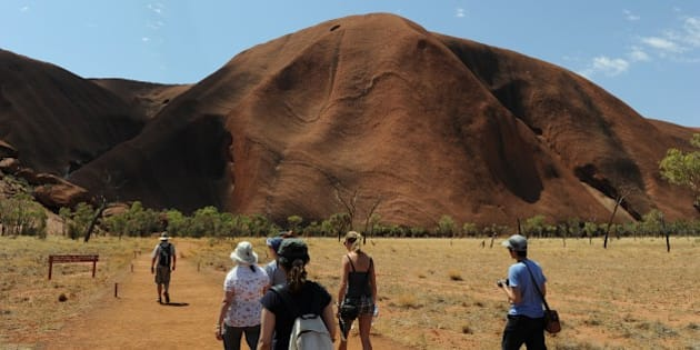 TO GO WITH STORY Australia-tourism-indigenous-Uluru,FEATURE by Madeleine Coorey This photo taken on October 11, 2013 shows tourists (below) walking towards Uluru, formerly known as Ayers Rock, a large sandstone rock formation and the world's largest monolith situated in the southern part of the Northern Territory in central Australia and southwest of the nearest large town Alice Springs. Tourists to Australia are increasingly seeking an Aboriginal experience and the ancient sacred site of Uluru is on their checklist, but while the traditional Aboriginal owners do not want tourists to climb the famous red monolith, some continue to do so, prompting a debate about whether the practice should be banned.    RESTRICTED TO EDITORIAL USE  -- IMAGE MUST BE USED WITH INTENDED AFP STORY UNDER AGREEMENT WITH NATIONAL PARKS AUSTRALIA --    AFP PHOTO / Greg WOOD        (Photo credit should read GREG WOOD/AFP/Getty Images)