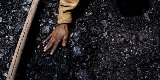 JAINTIA HILLS, INDIA - APRIL 16:  Thirty eight-year-old Prabhat Sinha, from Assam, levels out the coal in a crate on April 16, 2011 near the village of Khliehriat, in the district of Jaintia Hills, India. The Jaintia hills, located in India's far North East state of Meghalaya, miners descend to great depths on slippery, rickety wooden ladders. Children and adults squeeze into rat hole like tunnels in thousands of privately owned and unregulated mines, extracting coal with their hands or primitive tools and no safety equipment. Workers can earn as much as 150 USD per week or 30,000 Rupees per month, significantly higher than the national average of 15 USD per day. After traversing treacherous mountain roads, the coal is delivered to neighbouring Bangladesh and to Assam from where it is distributed all over India, to be used primarily for power generation and as a source of fuel in cement plants. Many workers leave homes in neighbouring states, and countries, like Bangladesh and Nepal, hoping to escape poverty and improve their quality of life. Some send money back to loved ones at home, whilst many others squander their earnings on alcohol, drugs and prostitution in the dusty, coal mining towns like Lad Rymbai. Some of the labor is forced, and an Indian NGO group, Impulse, estimates that 5,000 privately-owned coal mines in Jaintia Hills employed some 70,000 child miners. The government of Meghalaya refuted this figure, claiming that the mines had only 222 minor workers. Despite the ever present dangers and hardships, children, migrants and locals flock to the mines hoping to strike it rich in India's wild east. (Photo by Daniel Berehulak/Getty Images)