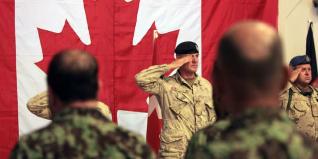 Brig.-Gen Dean Milner center, Commander of Canadian Forces Kandahar slaute along with others for Afghan and Canadian  anthem during a transfer of command authority ceremony in Kandahar airbase in Afghanistan, Thursday, July 7, 2011.Canadian combat operations have ended and their troops will transition to a non-combat training role with up to 950 soldiers and support staff to train Afghan soldiers and police in areas of the north, west and Kabul.((AP Photo/Rafiq Maqbool)