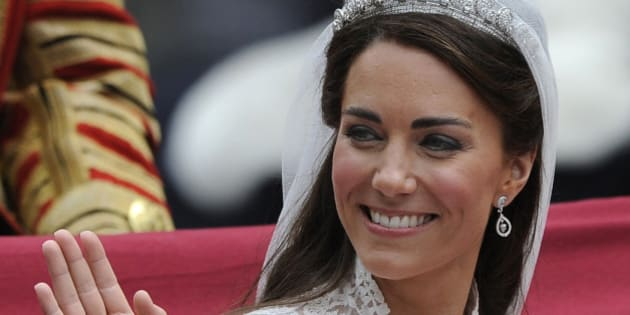 Britain's Catherine, Duchess of Cambridge, waves as she travels to Buckingham Palace in the 1902 State Landau, along the Procession Route, after her wedding to Britain's Prince William in Westminster Abbey, in central London April 29, 2011. (AP Photo/PAUL HACKETT, Pool)