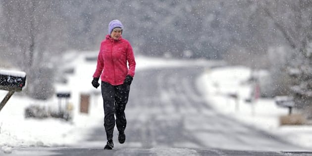 Sally Assmann runs through falling snow along Cambridge Drive in State College, Pa., Tuesday, Nov. 26, 2013. The first significant snowfall of the season fell overnight and continued through the morning. (Nabil K. Mark/Centre Daily Times/MCT via Getty Images)