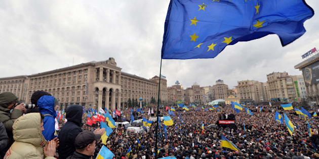 Ukrainian protesters wave a giant EU flag along with Ukrainian flags as thousands gather for an opposition rally at Independence Square in Kiev on December 1, 2013. About 100 police were injured in clashes that broke out as 100,000 outraged Ukrainians swarmed Kiev in a call for early elections meant to punish authorities for rejecting a historic EU pact. AFP PHOTO/ SERGEI SUPINSKY        (Photo credit should read SERGEI SUPINSKY/AFP/Getty Images)