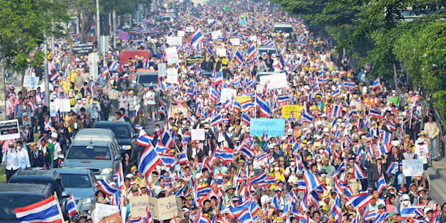 Thai anti government protesters wave national flags as they rallu at Government Complex in Bangkok on December 9, 2013.  Thai anti-government protesters vowed to keep up their fight to overthrow Prime Minister Yingluck Shinawatra despite her decision to call an election to try to end the kingdom's political crisis.     AFP PHOTO / PORNCHAI KITTIWONGSAKUL        (Photo credit should read PORNCHAI KITTIWONGSAKUL/AFP/Getty Images)