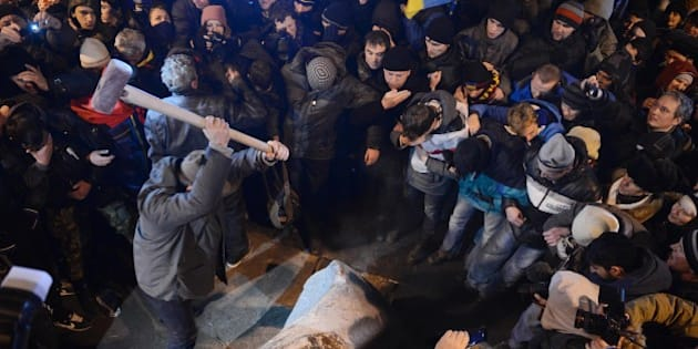 KIEV, UKRAINE - DECEMBER 8: An Ukrainian protester smashes Vladimir Lenin statue with sledgehammer as others watch after pull down the statue  in Besarabsky Square of Kiev, Ukraine, on December 8, 2013. Protestors continue their anti-government protests on Kiev. (Photo by Onur Coban/Anadolu Agency/Getty Images)