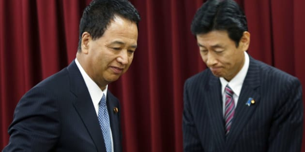 Akira Amari, Japan's minister of state for economic and fiscal policy, left, passes Yasutoshi Nishimura, Japan's deputy minister of state for economic and fiscal policy, during a news conference in Tokyo, Japan, on Thursday, Dec. 5, 2013. Amari said he will take leave for two weeks to receive treatment for early-stage cancer of the tongue. Photographer: Kiyoshi Ota/Bloomberg via Getty Images