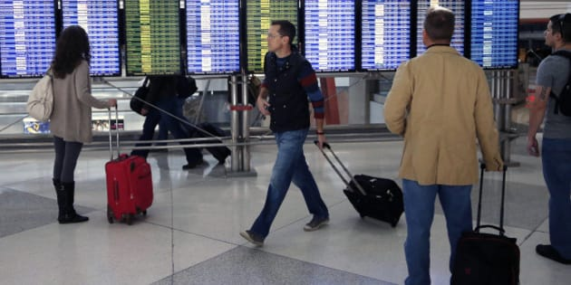 On the busiest travel day of the year, passengers check the departures board in a terminal at Denver International Airport, Wednesday, Nov. 27, 2013. More than 43 million people are to travel over the long holiday weekend, according to AAA. (AP Photo/Brennan Linsley)