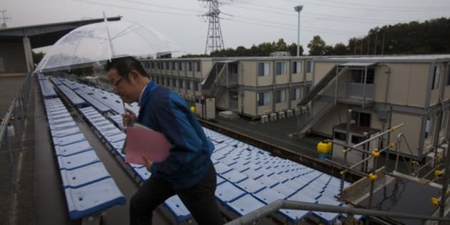 A employee of the Tokyo Electric Power Co. walks up stairs near temporary housing built for workers who live at J-Village, a soccer training complex now serving as an operation base for those battling Japan's nuclear disaster, in Fukushima, Japan, on Friday, Nov. 11, 2011. Tokyo Electric Power Co. is struggling to contain the worst nuclear disaster in 25 years. Photographer: David Guttenfelder/Pool via Bloomberg via Getty Images