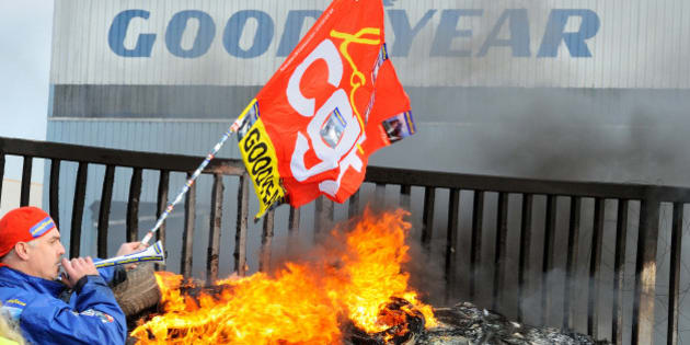 An employee waves a flag and blows a horn next to burning tyres in front the US Goodyear tyremaker site in Amiens, northern France, on December 5, 2013 after the announcement of the shutdown of the factory. AFP PHOTO DENIS CHARLET        (Photo credit should read DENIS CHARLET/AFP/Getty Images)