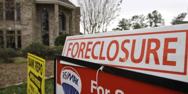 A bank repo and foreclosure for sale signs sit outside a foreclosed home Saturday, Jan. 10, 2009 in Houston.  (AP Photo/David J. Phillip)