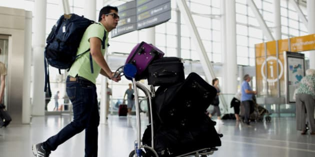 A traveler pushes a cart of luggage at Toronto Pearson International Airport in Toronto, Ontario, Canada, on Wednesday, July 3, 2013. Air Canada predicted further pressure on fares this year after its first-quarter yield dropped as competitors added seating and offered lower prices on some routes in North and South America. Photographer: Brent Lewin/Bloomberg via Getty Images
