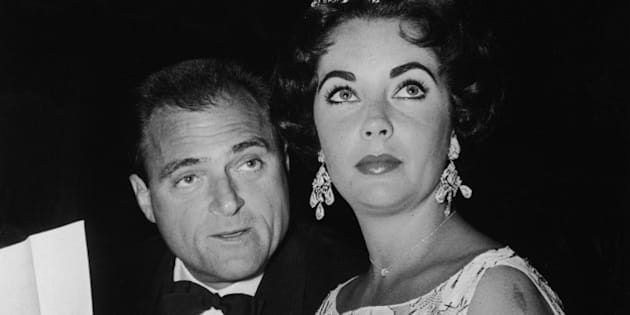 British-born actor Elizabeth Taylor sits with her third husband, American film producer Mike Todd (1909 - 1958), at a Golden Globe Awards ceremony at the Coconut Grove nightclub, Hollywood, California, 1957. (Photo by Hulton Archive/Getty Images)