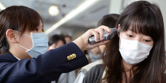 A passenger (R) has her temperature checked by a Centers for Disease Control (CDC) staff member at the entrance of Sungshan Airport in Taipei on April 4, 2013. Taiwan enhanced its level of alert against bird flu and set up a contingency centre after China's report of seven people infected with a new strain of avian influenza, including two deaths.  AFP PHOTO / Sam Yeh        (Photo credit should read SAM YEH/AFP/Getty Images)