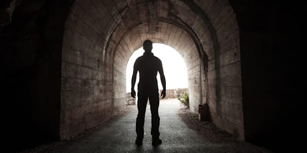 young man stands in dark tunnel ...