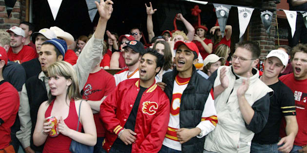 CALGARY, CANADA - JUNE 5:  Calgary Flames fans watching the game outside Melrose restuarant on 17th Avenue, also referred to as 'The Red Mile', react to a play against the Tampa Bay Lightning in game six of the NHL Stanley Cup Finals on June 5, 2004 at the Pengrowth Saddledome in Calgary, Canada. (Photo by Dave Buston/Getty Images)