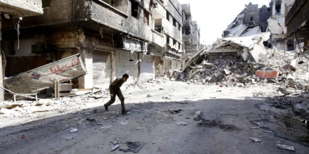 A fighter of the Popular Front for the Liberation of Palestine  General Command (PFLP-GC) runs across a street in the Yarmouk refugee camp in the Syrian capital Damascus on September 12, 2013, following fighting against rebel forces who control 75 percent of the camp. The PFLP-GC has been allied to Syrian President Bashar al-Assad's government whose troops have been fighting rebel forces for the past two years. AFP PHOTO/ANWAR AMRO        (Photo credit should read ANWAR AMRO/AFP/Getty Images)
